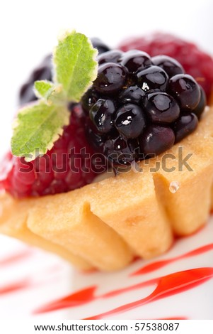 Closeup of delicious fresh berry cake garnished with pineapple mint - stock photo