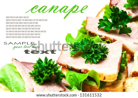 Closeup of delicious ham and salad canapes sandwiches with parsley lying on a white plate (with easy removable text). Horizontal. - stock photo