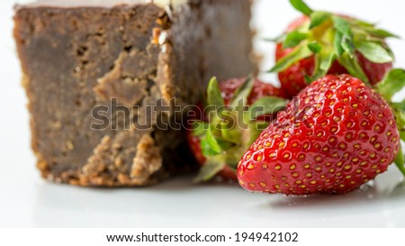 Closeup of delicious juicy red strawberries next to a piece of chocolate cake. - stock photo