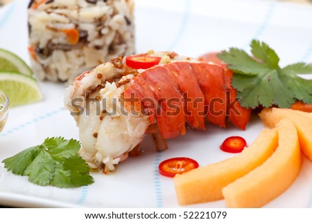 Closeup of delicious lobster tails served with spicy sauce, rice and melon - stock photo