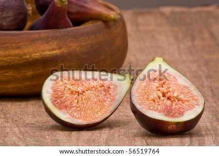 Closeup of delicious organic figs on table with wooden bowl