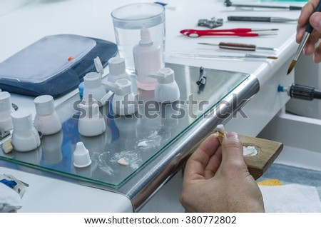 Closeup of dental technician applying ceramics to teeth before put into furnace