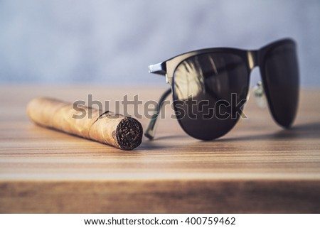 Closeup of desktop with sunglasses and cigar - stock photo