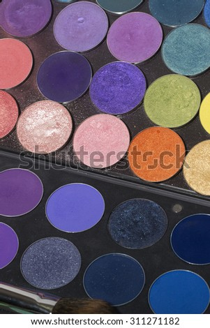 Closeup of different colorful set of professional palette of eyeshadow red orange green violet pink yellow purple black beige brown colors for  make-up, vertical picture - stock photo
