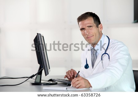 Closeup of doctor at his desk in front of computer