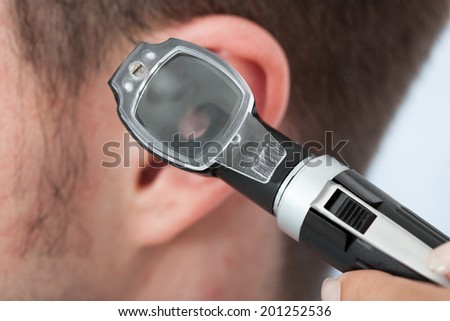 Closeup of doctor checking ear of male patient - stock photo