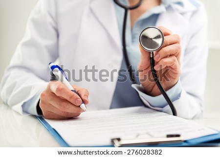 Closeup of doctor physician reporting medical test results. Woman medic in uniform filling health insurance document in the office.  Shallow depth of field.  - stock photo