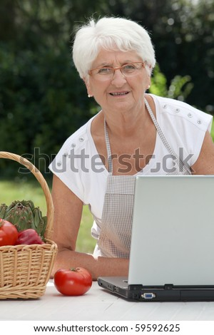 Closeup of elderly woman in garden with basket of fresh vegetables