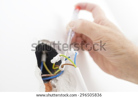 Closeup of electrician checking electrical current in a wire. Construction and building concept. - stock photo