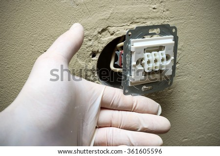 Closeup of electrician hands in gloves installing light switch in wall - stock photo