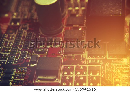 closeup of electronic circuit board with processor background retro effect image - stock photo