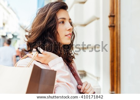 Closeup of elegant woman with shopping bag looking at boutique showcase - stock photo