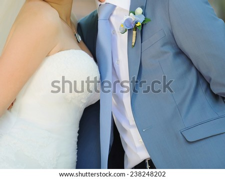 closeup of embracing bride and groom - stock photo