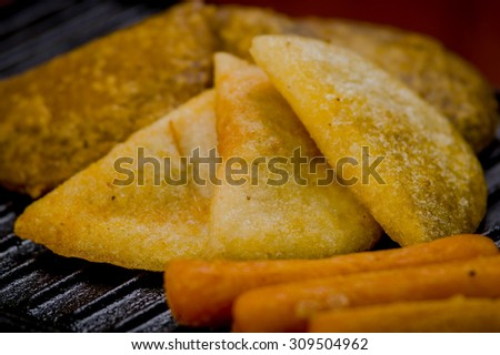 Closeup of empanadas, corn, cheese lying on black metal grill tablet. - stock photo
