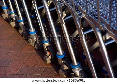 Closeup of empty shopping carts lined at the supermarket ready to be picked up - stock photo
