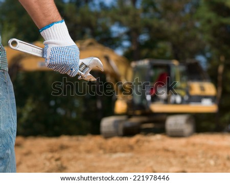 closeup of engineer hand holding french wrench on construction site outdoors - stock photo