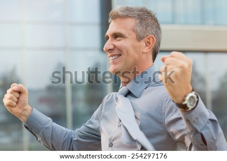 Closeup Of Exultant Businessman Clenching His Fist Outdoor - stock photo