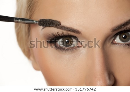 closeup of eyebrow shaping with brush - stock photo