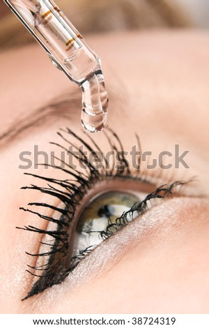 Closeup of eyedropper putting liquid into open eye - stock photo