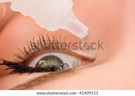 Closeup of eyedropper putting liquid into open eye. Top view - stock photo