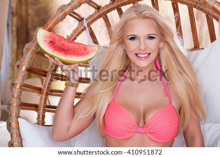 Closeup of fashion beautiful young blonde woman holding a watermelon slice. dressed in a bathing suit - stock photo