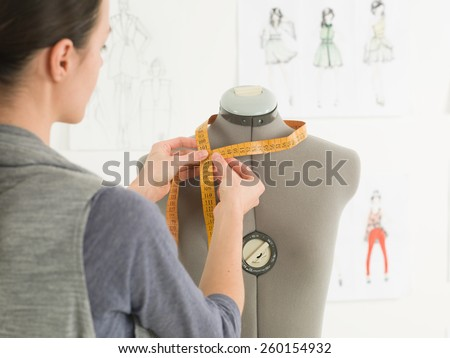 closeup of fashion designer measuring neck of dummy in a studio - stock photo