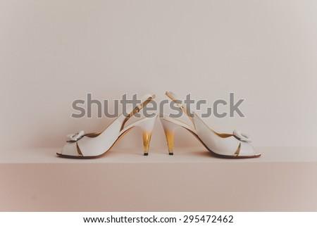 Closeup of fashionable bridal elegant white wedding shoes - stock photo