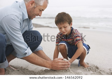 Closeup of father and son making sand castle together on beach - stock photo