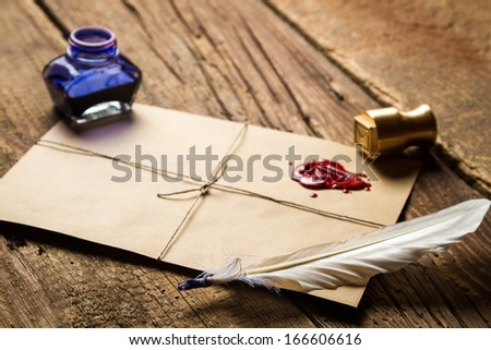 Closeup of feather on envelope with red sealant and inkwell - stock photo
