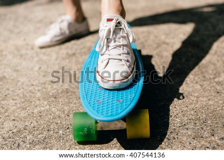Closeup of feet of a beautiful woman in white sneakers rides on blue penny skate board longboard with multi colored wheels. Urban scene, city life. Sport, fitness lifestyle. Cute hipster have fun.