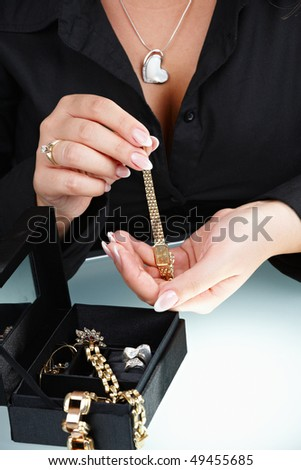 Closeup of femal hand taking out watch from jewelry box.