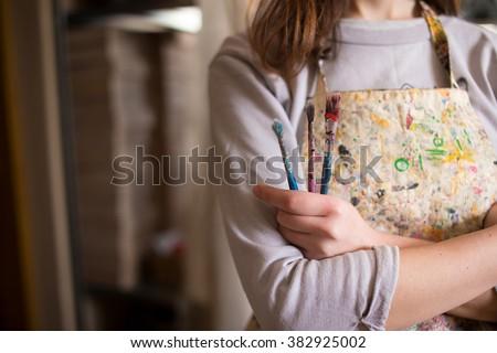 Closeup of female artist hand holding paintbrush - stock photo