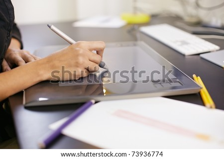 closeup of female dressmaker sketching and drawing dresses with graphic tablet. Horizontal shape, side view - stock photo