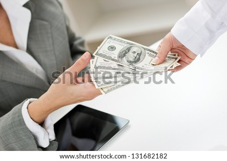Closeup of female hand giving money. - stock photo