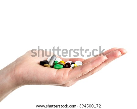 Closeup of female hand holding all sorts of pilss and tablets on white background - stock photo