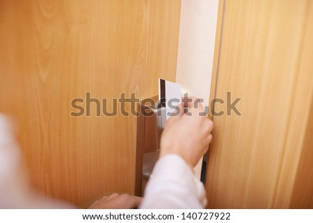 Closeup of female hand holding cardkey and opening door of hotel room - stock photo