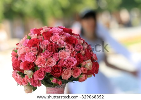 Closeup of female hand holding one big beautiful colorful soft aroma fresh wedding bouquet of many pink and purple rose flowers sunny day outdoor on natural background, horizontal picture - stock photo