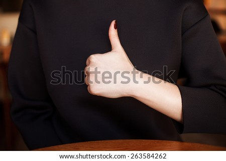 Closeup of female hand showing thumbs up sign on black - stock photo