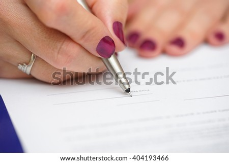 closeup of female hand signing document