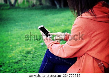 Closeup of female hand using a mobile phone on farm background - stock photo