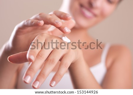 closeup of female hands applying hand cream - stock photo