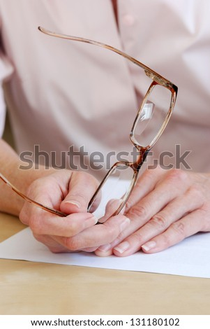 Closeup of female hands holding a pair of bifocal eyeglasses - stock photo