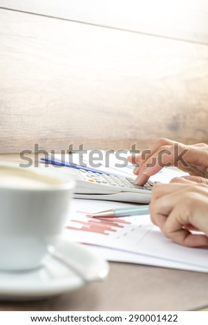 Closeup of female hands making mathematical and statistical calculations on white desk calculator while proofreading financial graphs with a cup of hot coffee alongside.