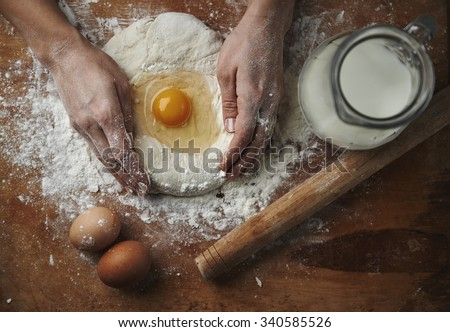Closeup of female hands mixing dough with egg and flour on wooden board in rustic kitchen. - stock photo