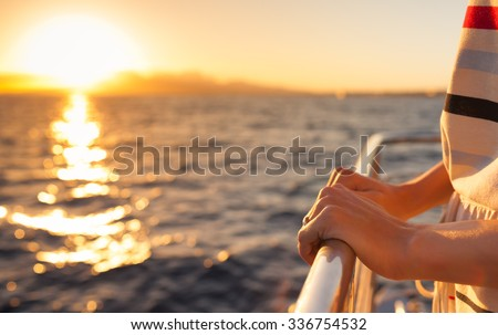 Closeup of female hands on a yacht during sunset.   - stock photo