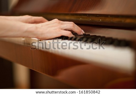 Closeup of female hands playing the piano - stock photo