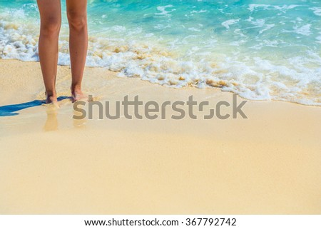 Closeup of female legs on tropical beach. Women's legs on the sand. Copy space too. - stock photo