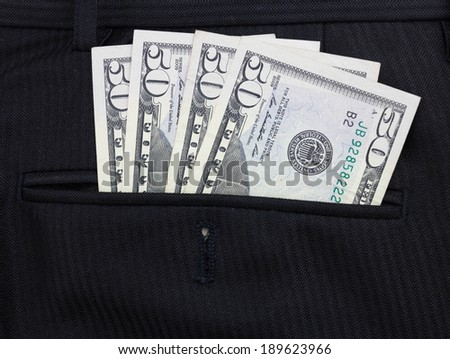 Closeup of fify dollar bills in suit pocket - stock photo
