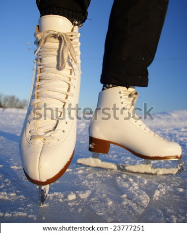Closeup of figure skating ice skates in action outdoors - stock photo