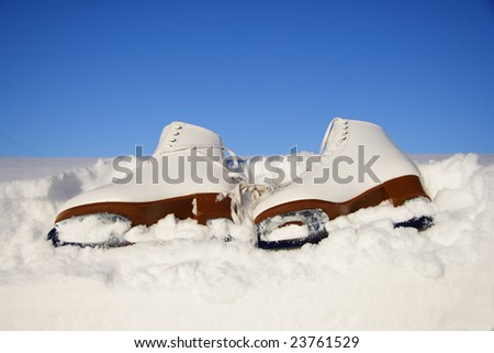 Closeup of figure skating ice skates lying in the snow outdoors - stock photo